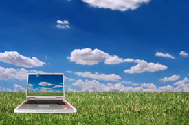 Computer setting on grass with beautiful blue sky and white clouds in background